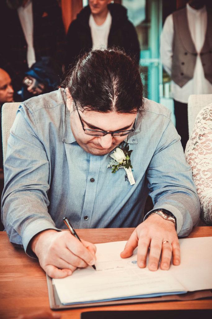 Der Bräutigam gibt seine Unterschrift zur Hochzeit.