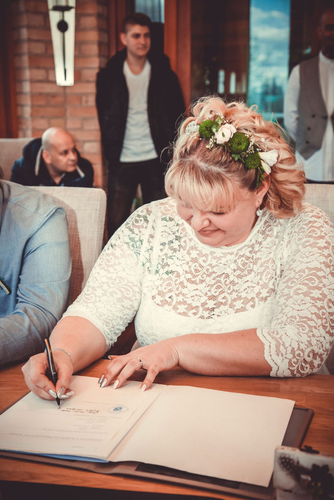 Die Braut gibt ihre Unterschrift zur Hochzeit.