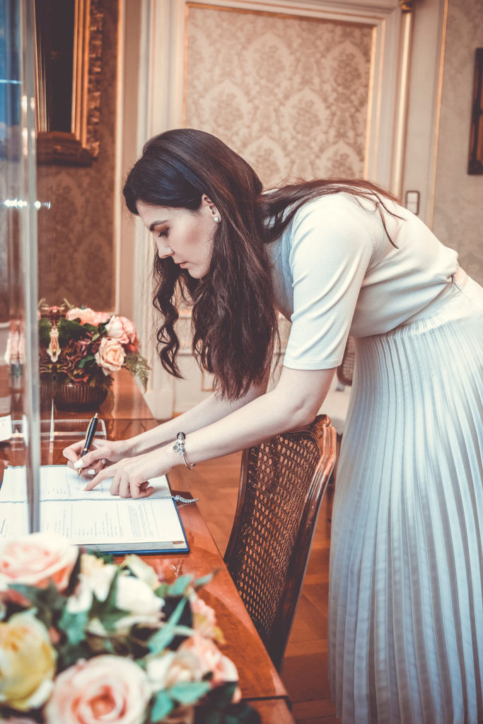 Braut setzt seine Unterschrift auf dem Dokument