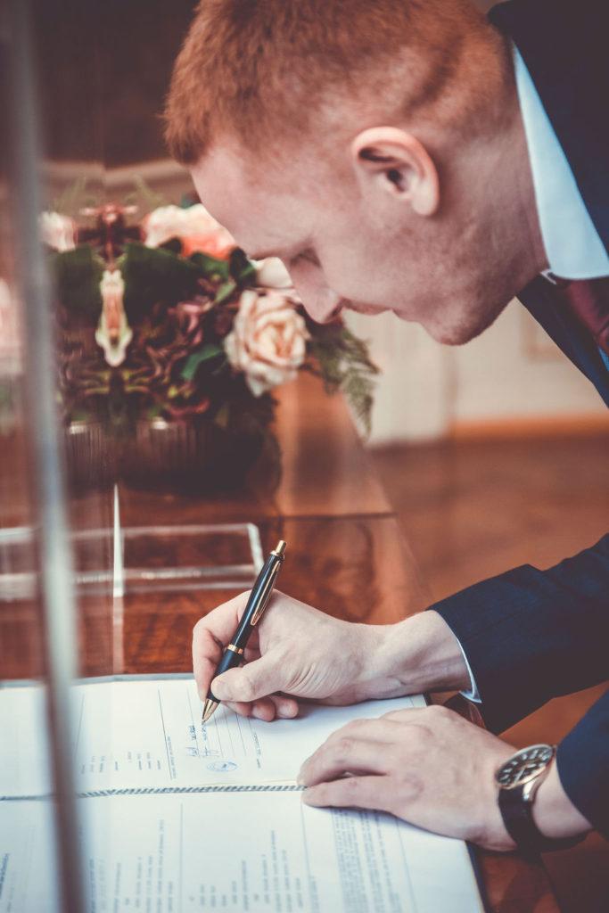 Bräutigam setzt seine Unterschrift auf dem Dokument