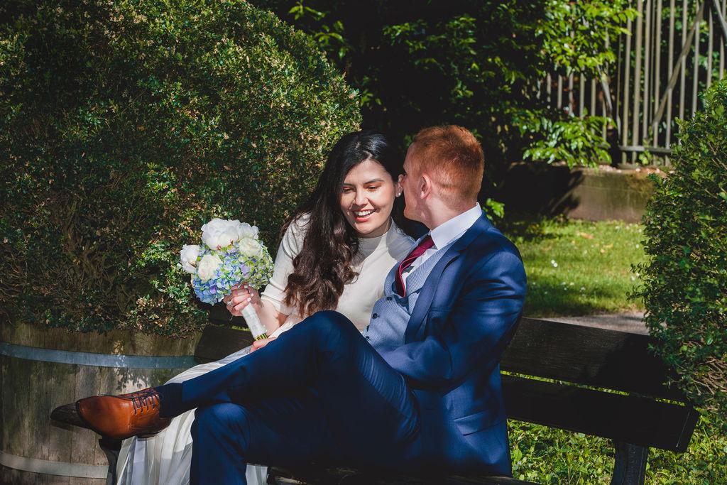 Braut und Bräutigam mit dem Blumenstrauß der Braut draußen sitzend auf Bank und Händchenhalten