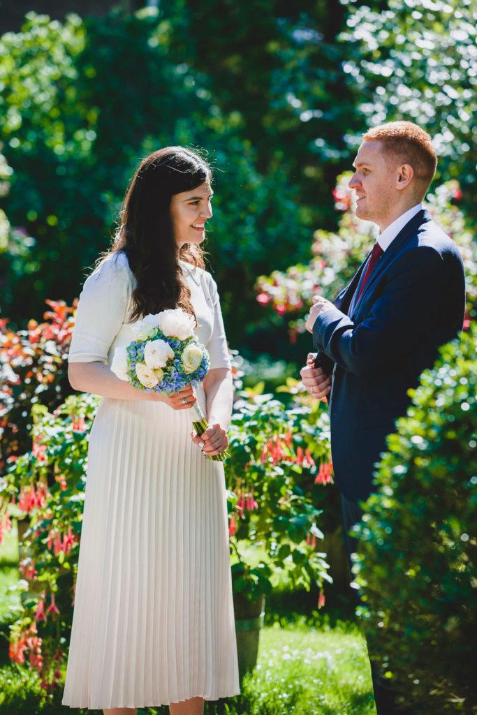 Das Brautpaar sitzt zusammen in einer Blumenwiese.