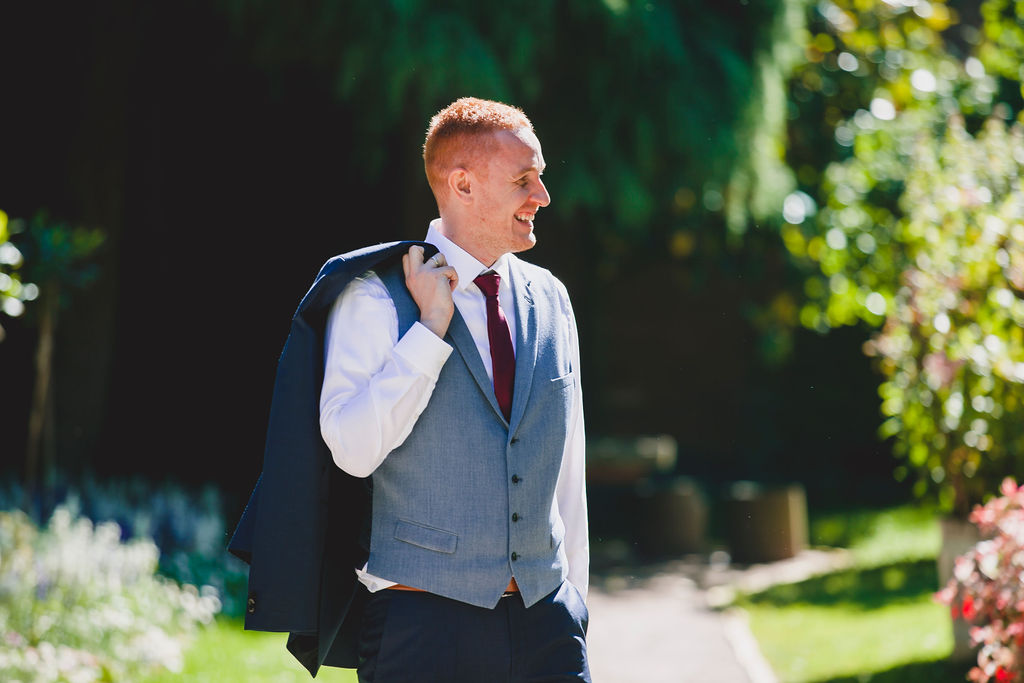 Stilvoller hübscher Bräutigam, der, im selbstbewussten Anzug schaut.
