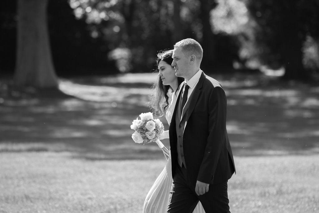 Die Braut und der Bräutigam gehen Händchenhalten im Park
